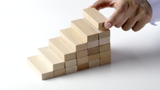 businessman placing last wooden block to complete staircase, show growth and improvement - a forma di blocco video stock e b–roll