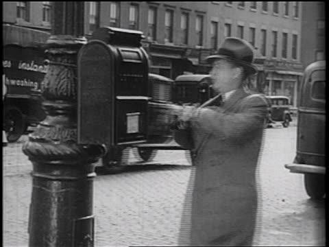 stockvideo's en b-roll-footage met b/w 1936 businessman placing letter in mailbox on street corner / documentary - minder dan 10 seconden