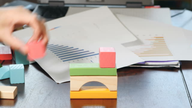 businessman  play toy blocks against business charts - toy block stock videos and b-roll footage