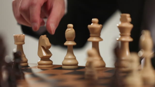 businessman playing chess and holding a piece - chess piece stock videos & royalty-free footage