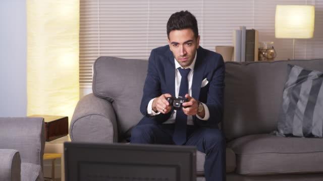 businessman playing video games at home - プエルトリコ人点の映像素材/bロール