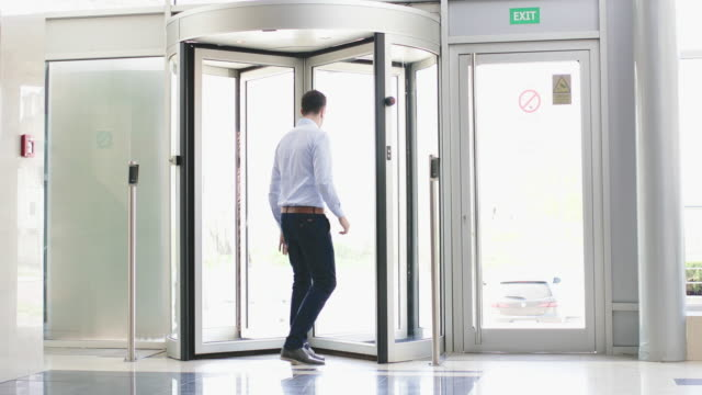 businessman playing with revolving door - bloccato video stock e b–roll