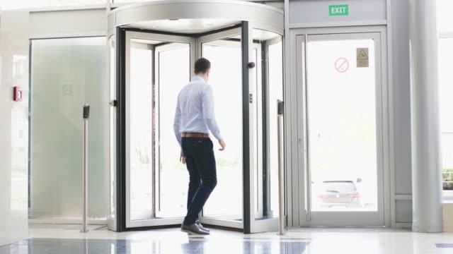 stockvideo's en b-roll-footage met zakenman spelen met draaideur - klem