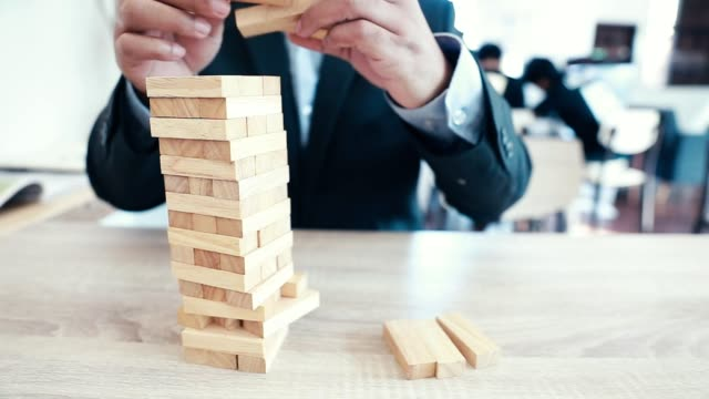 businessman playing wooden block building collapse - toy block stock videos and b-roll footage