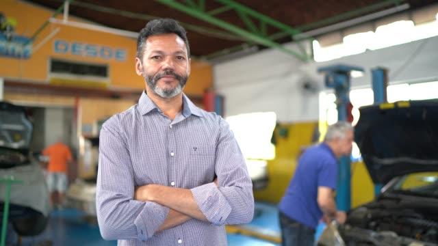 vídeos de stock e filmes b-roll de businessman portrait in auto repair shop - em frente de