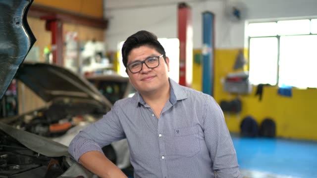 businessman portrait in auto repair shop - davanti video stock e b–roll