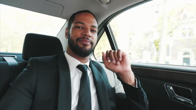 vidéos et rushes de portrait d'homme d'affaires voyageant en voiture. - intérieur de véhicule