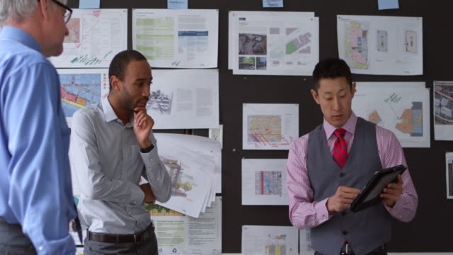 MS Businessman presenting project on digital tablet to coworkers in office