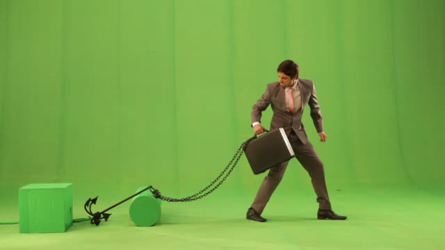 Businessman pulling his briefcase tied with a chain