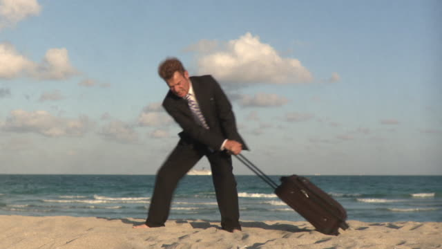 WS Businessman pulling luggage on beach / South Beach, Florida, USA