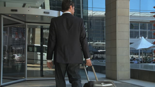 ms pan businessman pulling suitcase and walking into hotel / cape town, cape town, south africa - eingang stock-videos und b-roll-filmmaterial