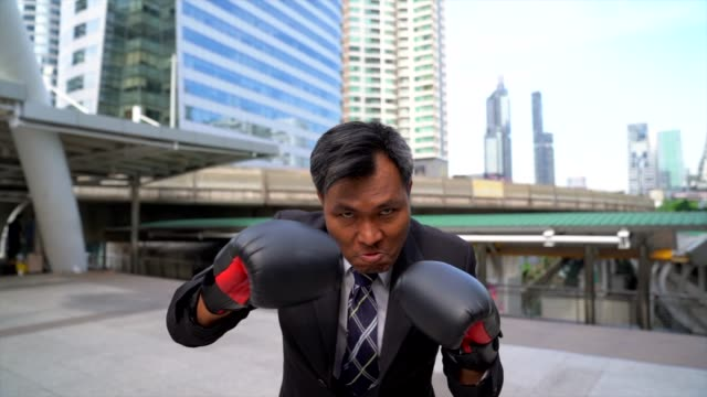 businessman punching with boxing gloves. concept of business competition.front view of businessman in boxing gloves against outdoor with cityscape as background. - punching stock videos & royalty-free footage