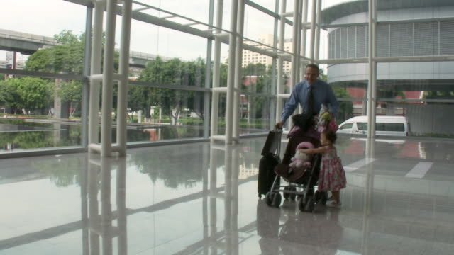 MS PAN Businessman pushing baby stroller with daughter (2-3) running by in lobby / Bangkok, Thailand