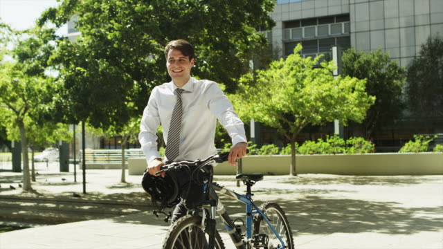 WS MS of businessman pushing bicycle outdoors