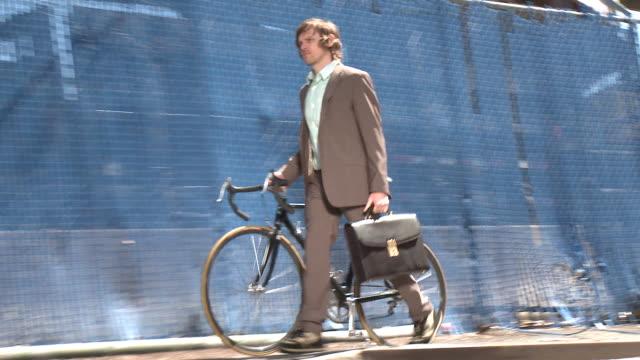 WS ZO PAN ZI MS Businessman pushing bike, New York City, New York, USA