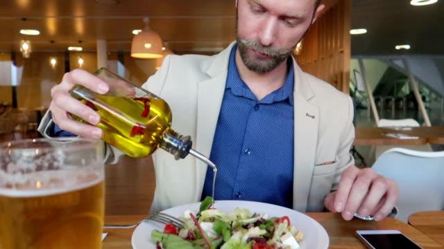 vídeos y material grabado en eventos de stock de empresario puso aceite de oliva en una ensalada-stock video - voz