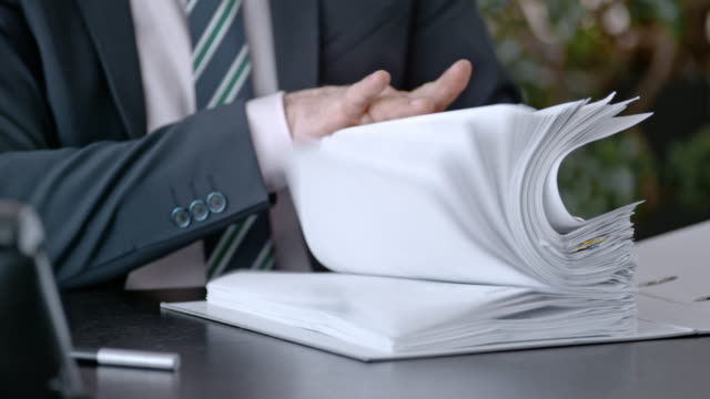 slo mo businessman putting a binder into the trash - lanciare video stock e b–roll