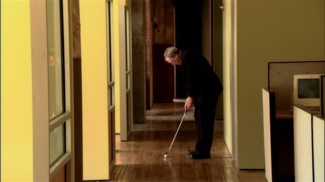 ws businessman putting golf ball in office hallway/ man walking and smiling with club over shoulder  - golf club stock videos & royalty-free footage