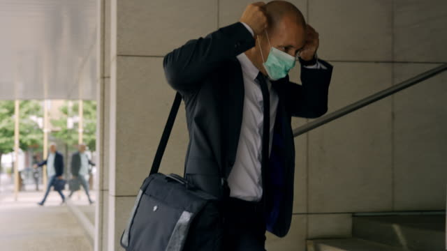 vídeos de stock e filmes b-roll de slo mo businessman putting on a mask while entering the office building - formal