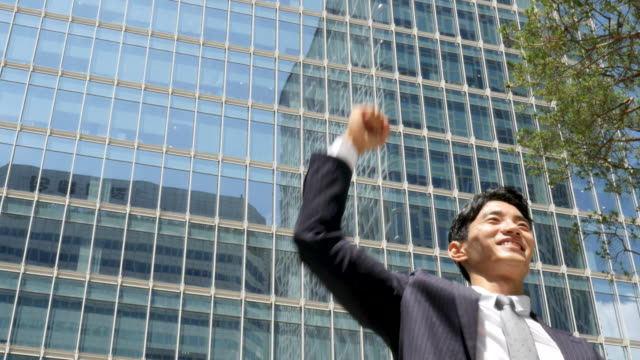 businessman raising fist in the air for cheering up - menschliche gliedmaßen stock-videos und b-roll-filmmaterial