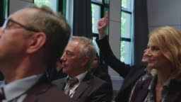 Businessman raising hand amidst colleagues