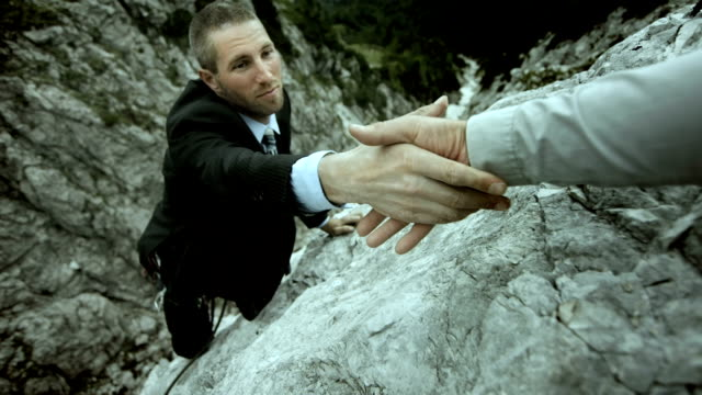 hd: businessman reaching for a helping hand - cliff stock videos & royalty-free footage