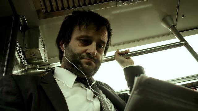 vidéos et rushes de hd: homme d'affaires lire un journal sur le métro - costume complet
