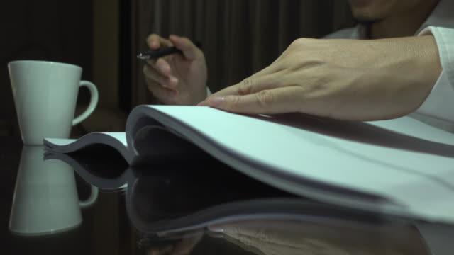 ビジネスマンは夜にノートを読んでメモを取る - 30代点の映像素材/bロール