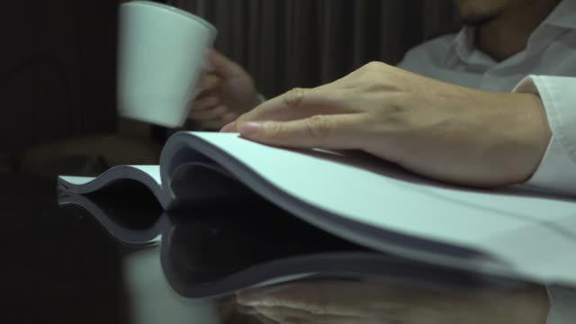 ビジネスマンが本を読んだり、夜に飲んだりする - 30代点の映像素材/bロール