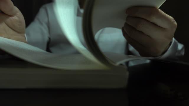 ビジネスマンは夜に素早く本を読む - 30代点の映像素材/bロール