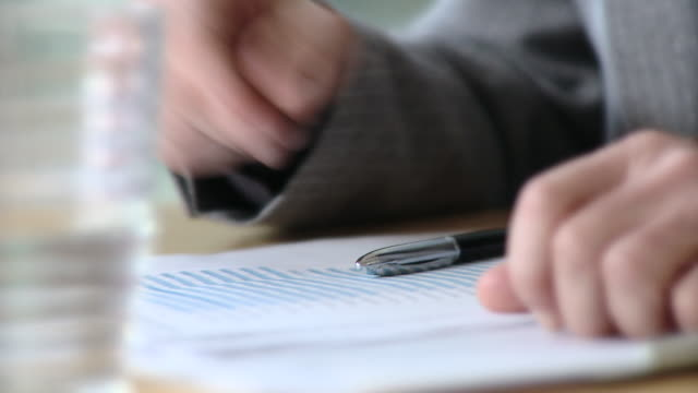 vidéos et rushes de cu selective focus businessman reading document and pointing with pen / berlin, germany - feuille papier
