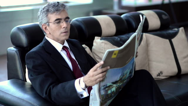 MS Businessman reading newspaper and looking at his wristwatch at airport / India