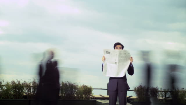 vídeos de stock e filmes b-roll de businessman reading newspaper as commuters pass at speed, time lapse - parado