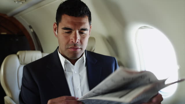 ms businessman reading newspaper in airplane / spanish fork, utah, usa - geschäftsreise stock-videos und b-roll-filmmaterial