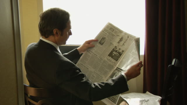 ms, businessman reading newspaper in hotel dining room, rear view - reading stock videos & royalty-free footage