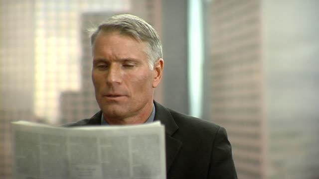 cu businessman reading newspaper in office, los angeles, california, usa - hel kostym bildbanksvideor och videomaterial från bakom kulisserna