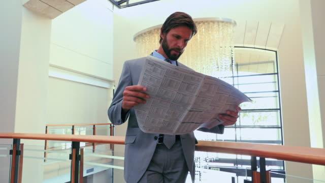 stockvideo's en b-roll-footage met businessman reading newspaper - financiële pagina