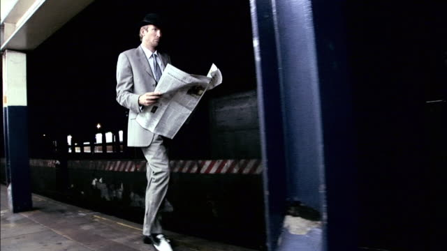 ws businessman reading newspaper while walking in subway station / new york city, new york, usa - film noir style stock videos & royalty-free footage
