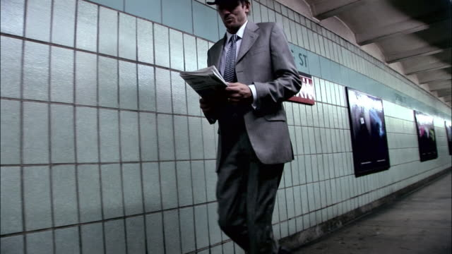 la ws businessman reading newspaper while walking in subway station past spring street sign / manhattan, new york, new york, usa - multi tasking stock videos & royalty-free footage