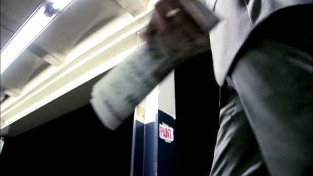 la ms businessman reading newspaper while walking on subway platform at night / new york city, new york, usa - freshly painted stock videos & royalty-free footage