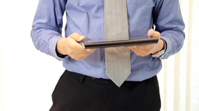 vidéos et rushes de homme d'affaires lecture sur tablet pc dans le bureau - costume complet