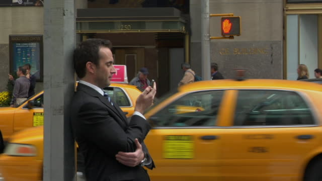 vídeos y material grabado en eventos de stock de t/l ms businessman reading text message on his cell phone while pedestrians and traffic cross street / new york, new york, usa - t mobile