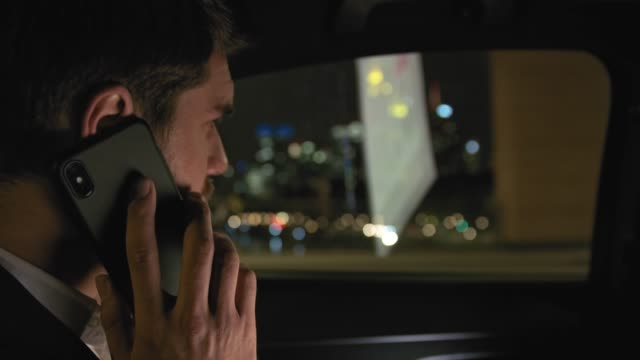 businessman receiving call in car at night in city - handsome people stock videos & royalty-free footage