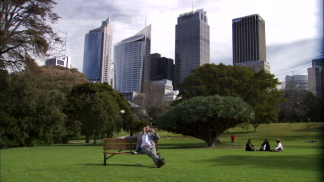 vídeos de stock e filmes b-roll de ws, businessman reclining on bench in park and talking on mobile phone, office buildings in background, sydney, australia - parque público
