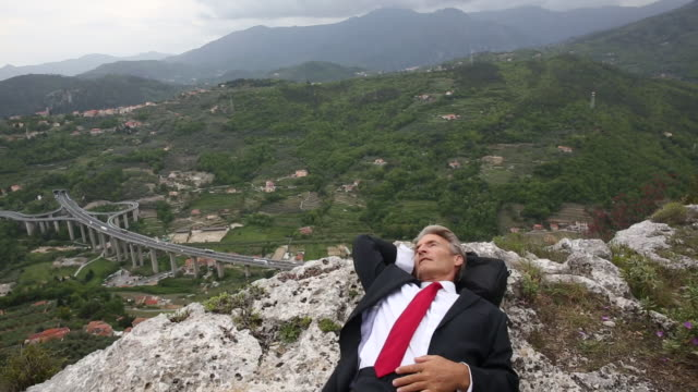 businessman relaxes on rocky ledge, above valley - kompletter anzug stock-videos und b-roll-filmmaterial