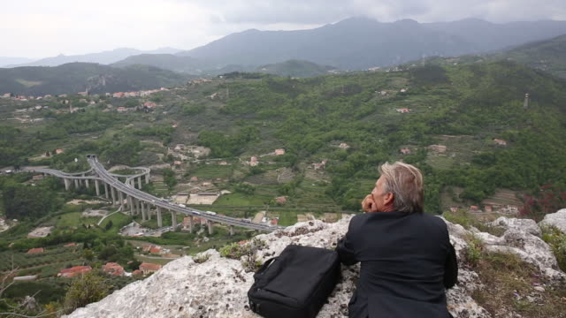 businessman relaxes on rocky ledge, above valley - one mature man only stock videos & royalty-free footage