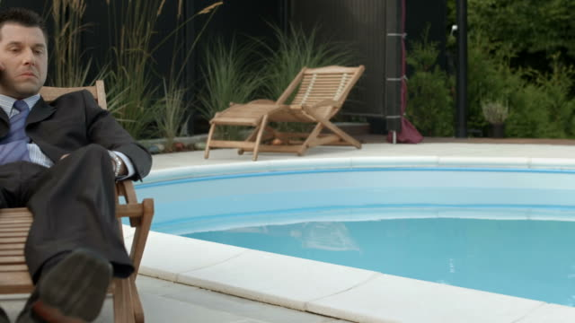 hd dolly: businessman relaxing by the pool - hanging up stock videos and b-roll footage