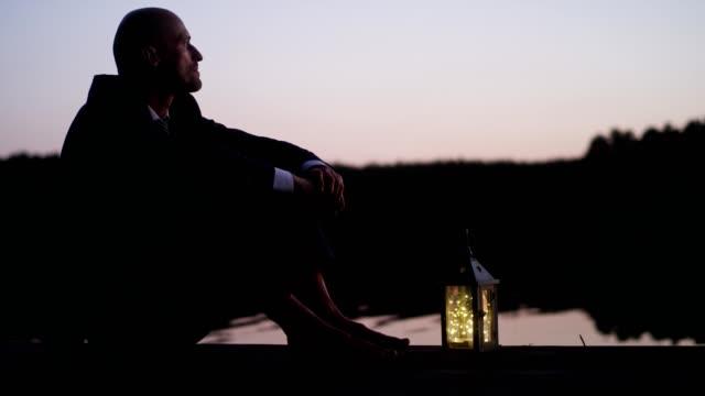 vídeos de stock e filmes b-roll de businessman relaxing on a lake pier - zen