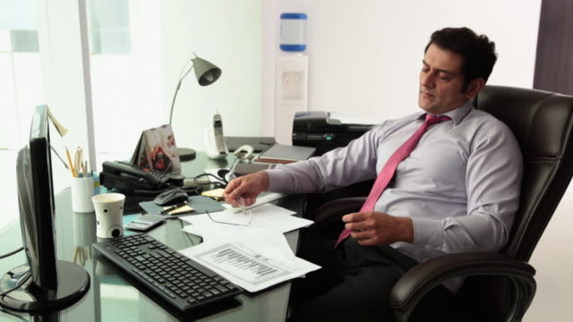 businessman relaxing on the chair  - コードレスフォン点の映像素材/bロール