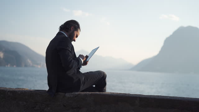 businessman remote working from beach using tablet, view of lake and mountains behind - one mid adult man only stock videos & royalty-free footage